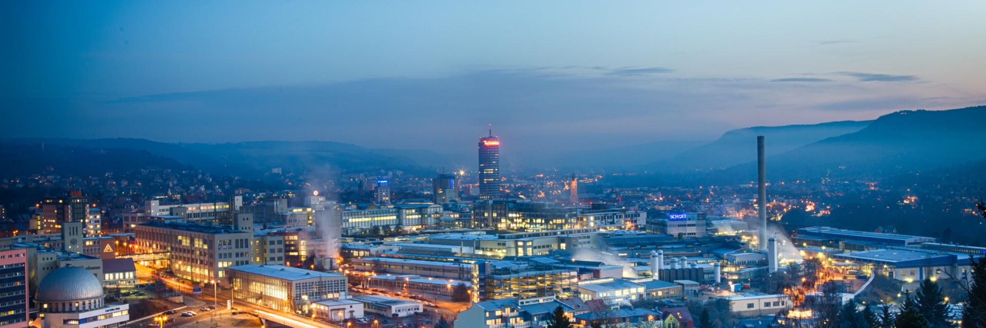 Stadtansicht vom Waldrand auf das beleuchtete Zeiss und Schott Gelände © JenaKultur , Foto: André Gräf