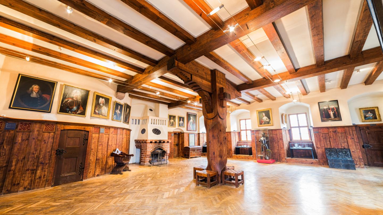 Leuchtenburg: Leerer Rittersaal mit Fachwerkdecke und mittelalterlichen Ausstellungstücken neben einem alten Kamin © Stiftung Leuchtenburg Foto: Daniel Hofmann