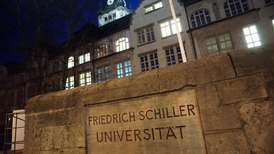 Hauptgebäude der Friedrich-Schiller-Universität Jena bei Nacht mit Steintafel im Vordergrund
