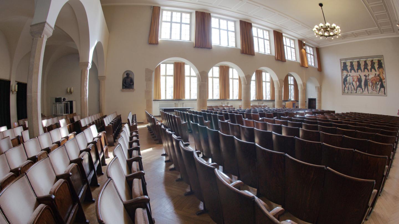 Lichtdurchflutete Aula der Universität Jena mit Säulengang und Wandgemälde