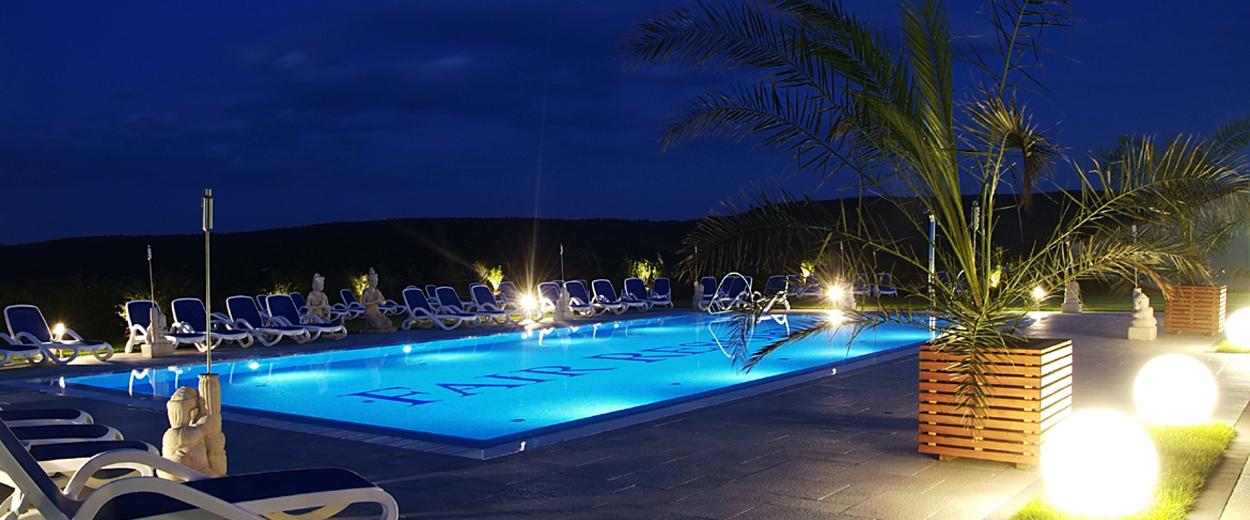 Außenterasse mit Pool bei Nacht