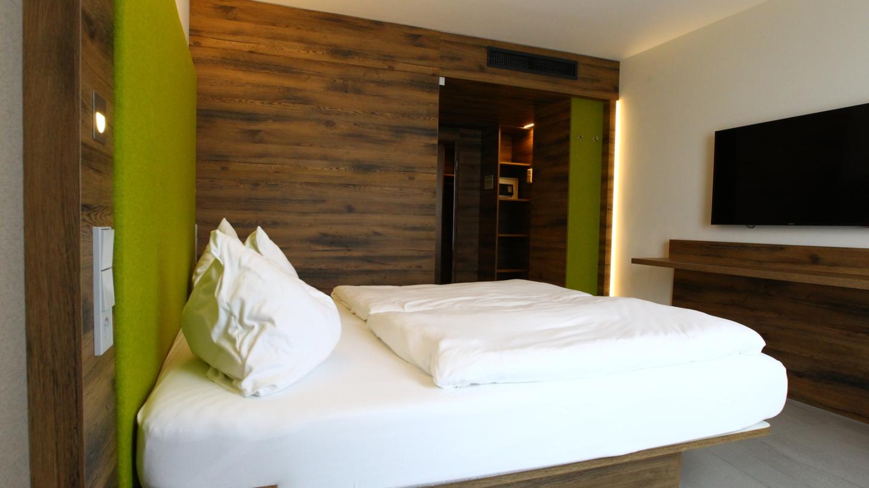 Hotelzimmer mit Doppelbett und Flachbild Fernseher