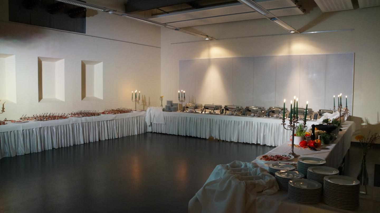 Raum mit Buffetstrecke in U-Form mit Kerzenständern und einer Auswahl an kalten und warmen Speisen