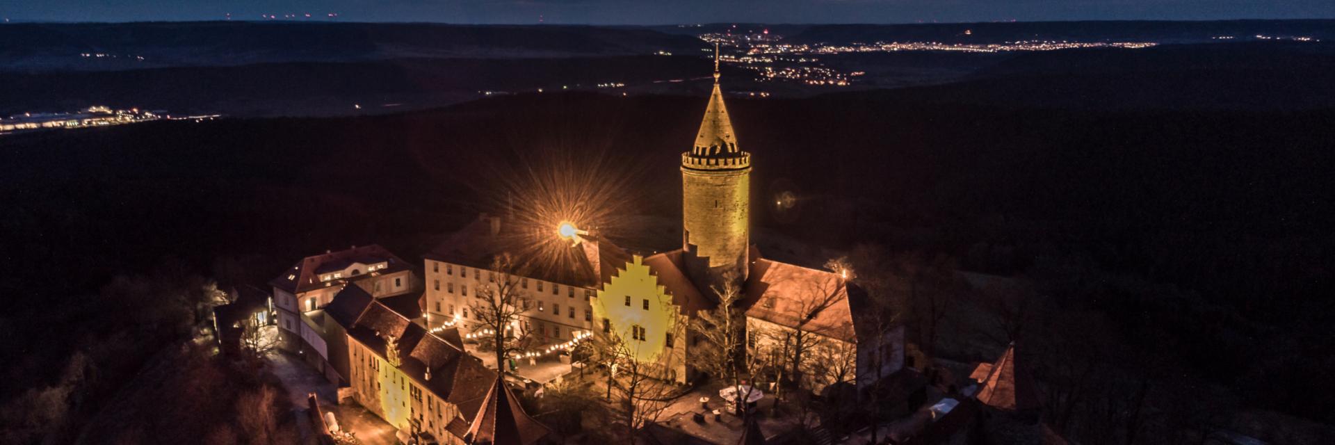 Luftaufnahme der Leuchtenburg bei Nacht mit Jena am Horizont © Stiftung Leuchtenburg, Foto: Daniel Suppe