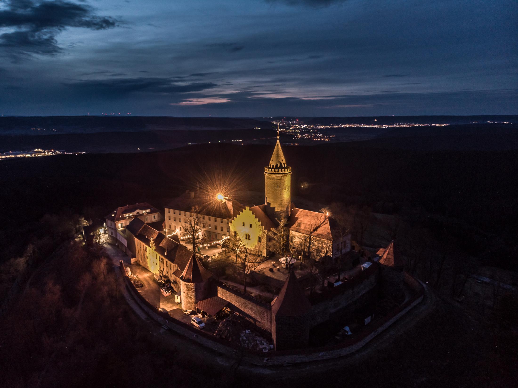 Luftaufnahme der Leuchtenburg bei Nacht mit Jena am Horizont