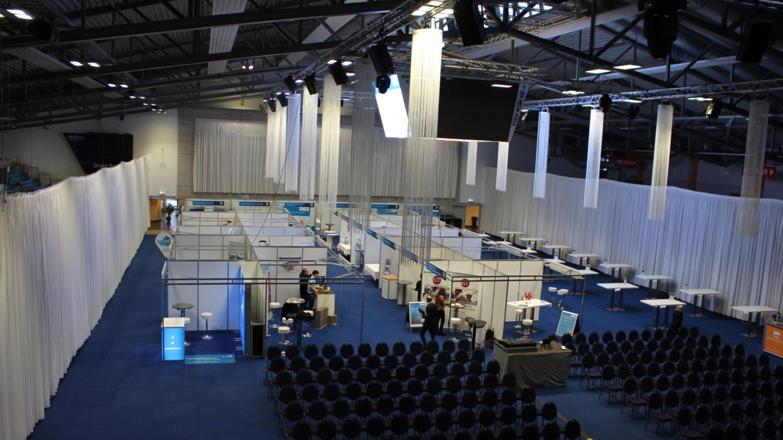 Messestände im Aufbau in einer mit Fadenvorhängen dekorierten Sparkassen-Arena Jena