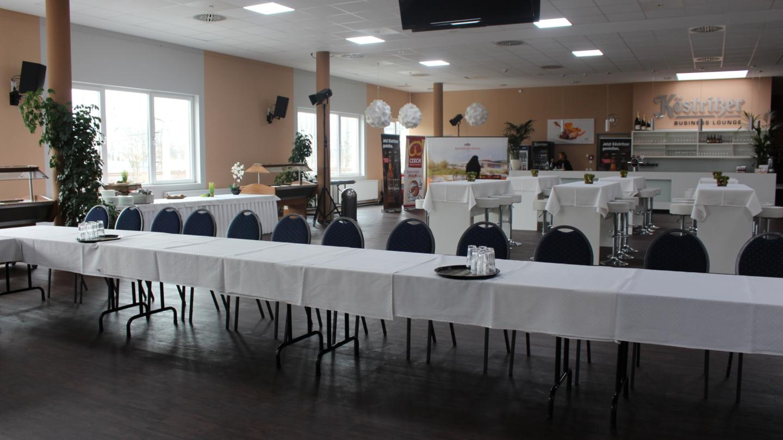 Für eine Tagung eingerichtete Lounge mit Tischen und Catering-Bereich