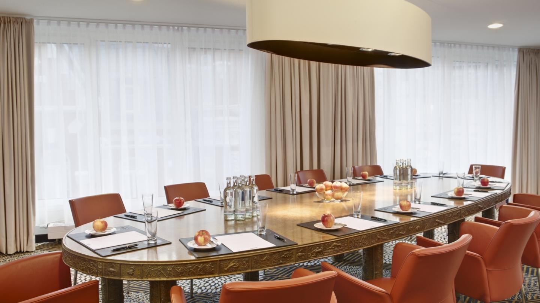 Langer ovaler Konferenztisch mit Schreibutensilien, Getränken und Äpfeln