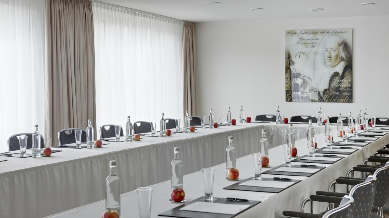 Raum in U-Bestuhlung mit Schreibutensilien, Getränken und ein Portrait von Hölderlin im Hintergrund