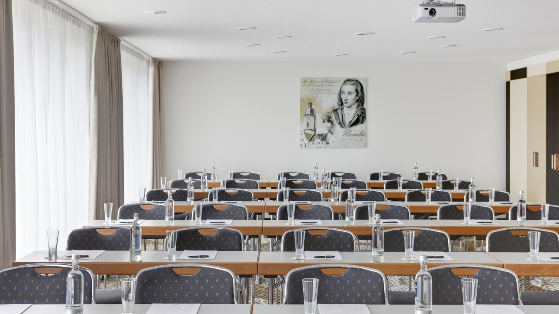 Raum in Parlament-Bestuhlung mit Schreibutensilien, Getränken und eine Portrait von Novalis im Hintergrund