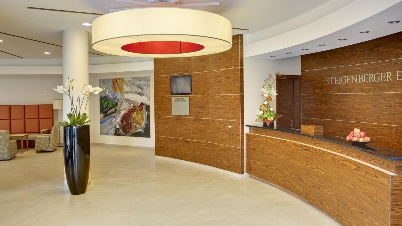 Hotelrezeption mit Sitzecke, Blumenvasen und Gemälde an der Wand
