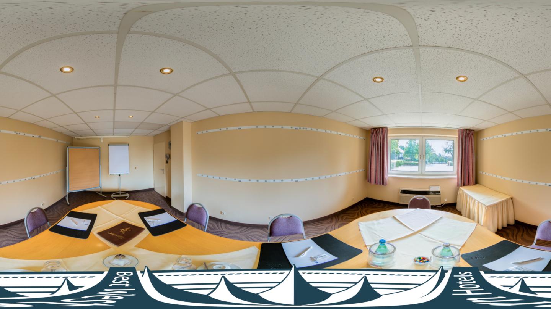 Konferenzraum 3 mit langem Tisch, Pinnwand und Flipchart