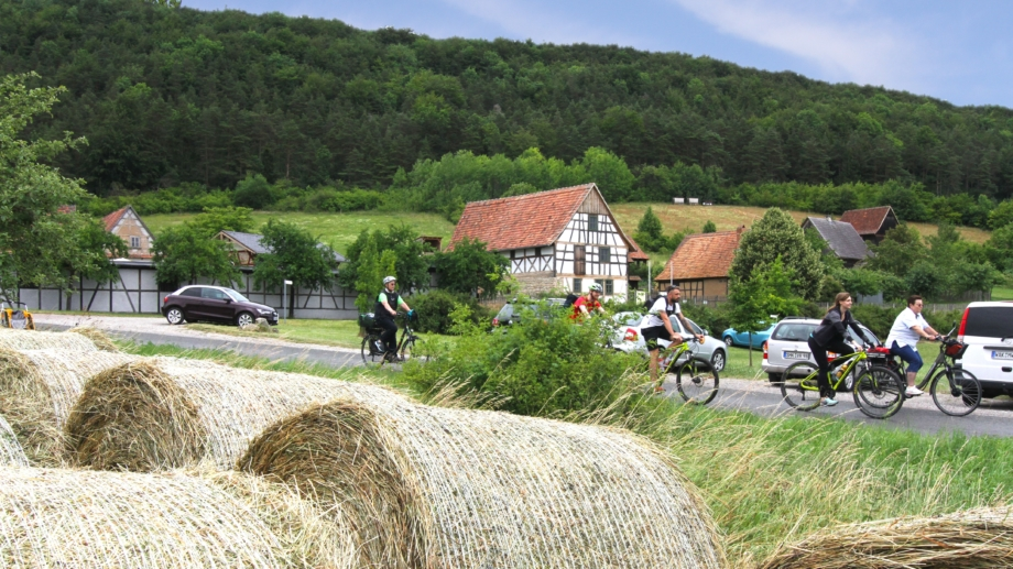 Radfahrer vor dem Thüringer Freilichtmuseum Hohenfelden mit Strohballen im Vordergrund © Landratsamt Weimarer Land, Foto: Uwe Germar