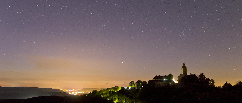 Blick auf die Leuchtenburg unter Sternenhimmel mit Lichtstadt Jena im Hintergrund - Ausflüge rund um Jena © Stiftung Leuchtenburg, Foto: Alexander Schlotter