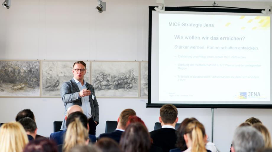 Redner präsentiert die Tagesagenda auf einer Leinwand den Teilnehmern der Tagungsallianz Jena © JenaKultur, Foto: Christoph Worsch