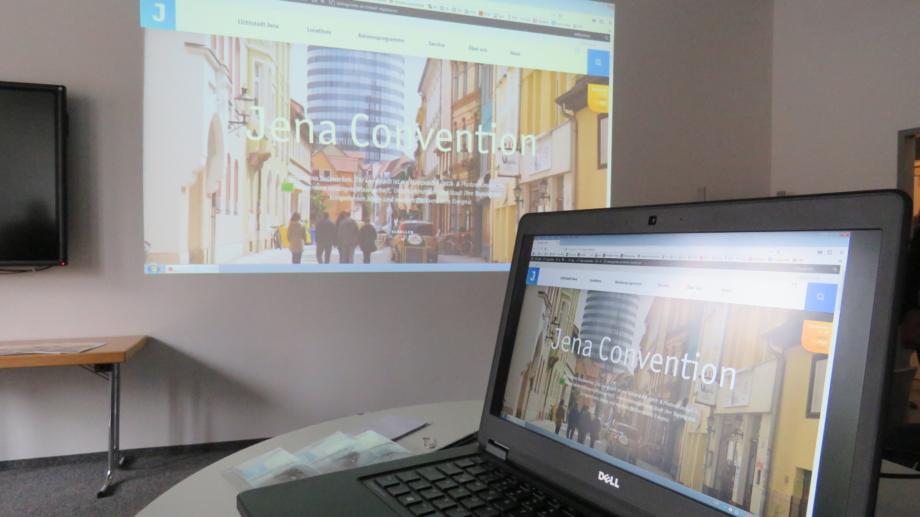Laptop und Leinwand zur Vorstellung des neuen MICE-Portals