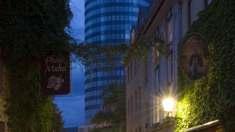 Kulinarische Stadtführung: Die Wagnergasse in Jena bei Abendstimmung - Restaurantbesucher sitzen draussen und im Hintergrund leuchtet dies Fassade des JenTowers.