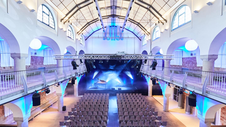 Blick von der Galerie auf die Bühne mit Konzertflügel und Lichtinszenierung